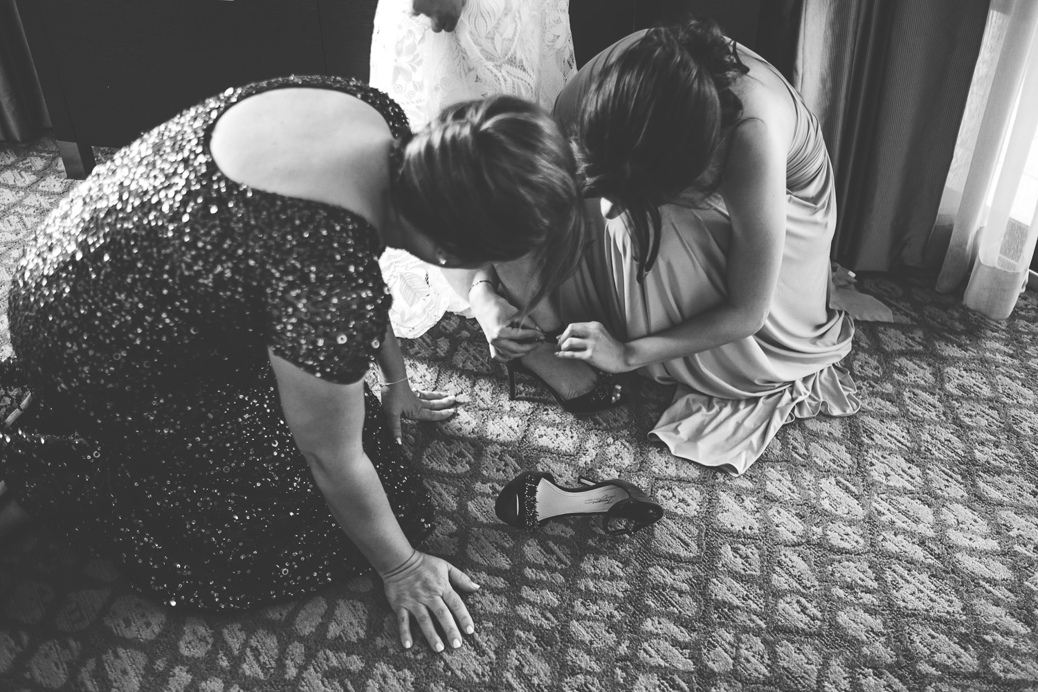 mom and sister helping bride put on shoes