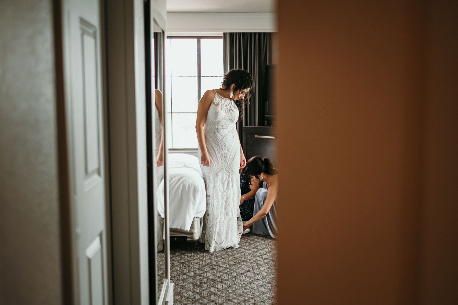 sneaky shot from other room of bride putting on shoes