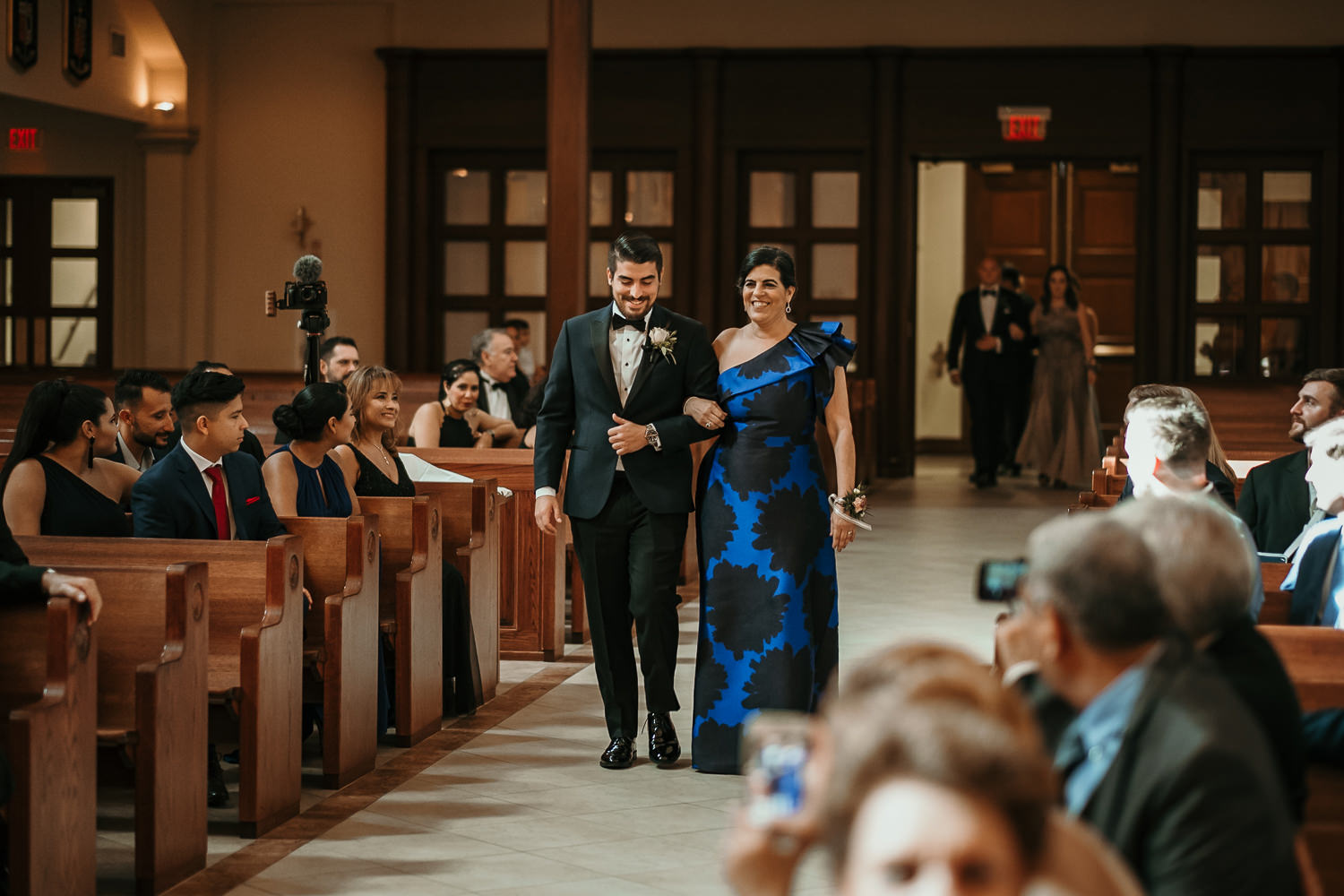 groom escorting mother down aisle
