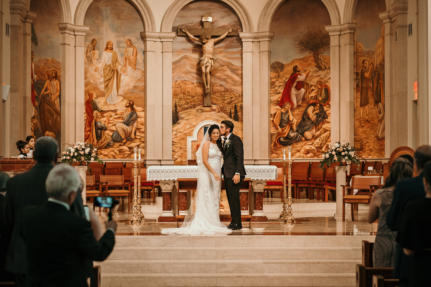 wide picture groom kissing brides forehead on church altar