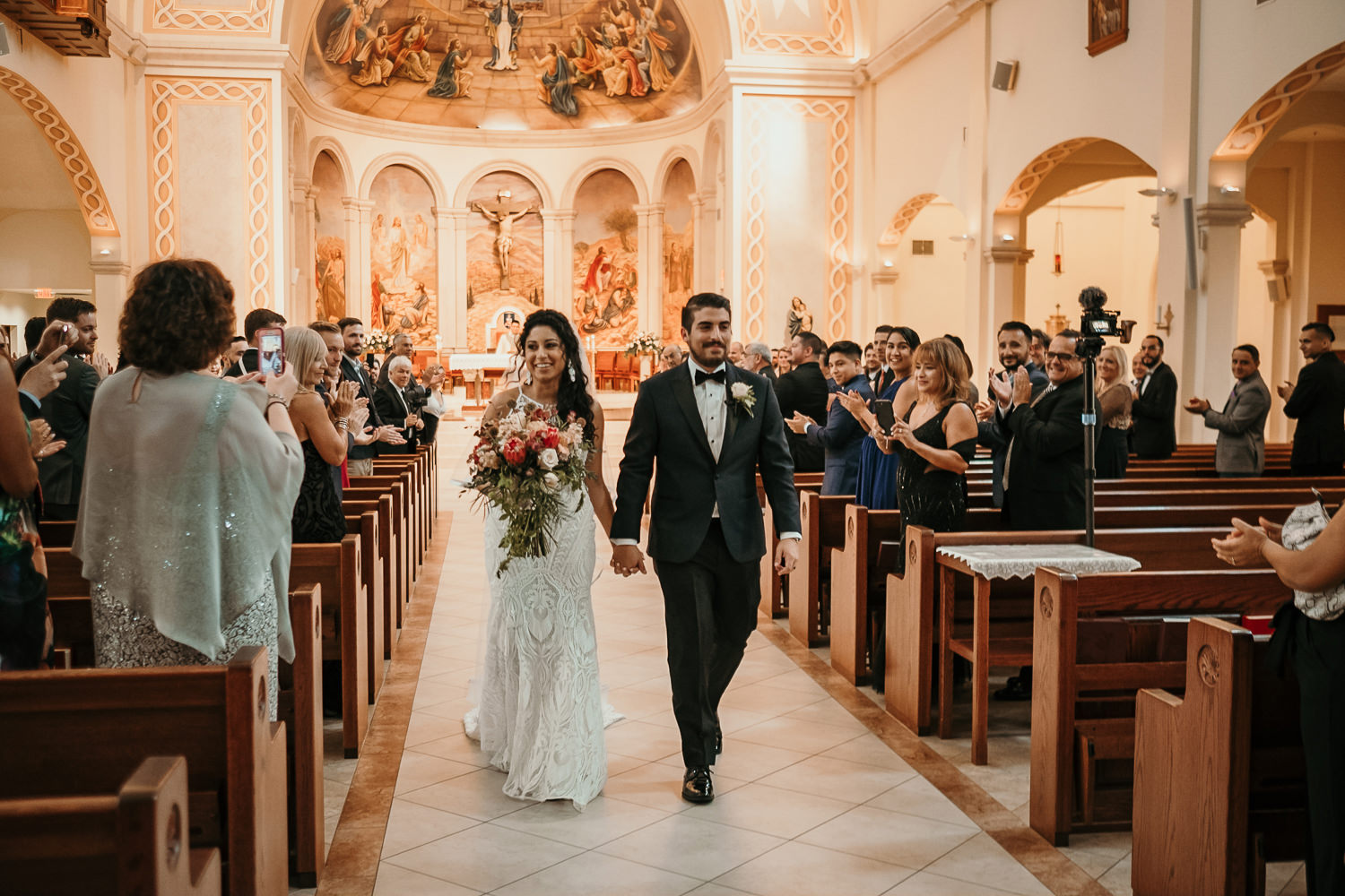 newlyweds walking down church aisle