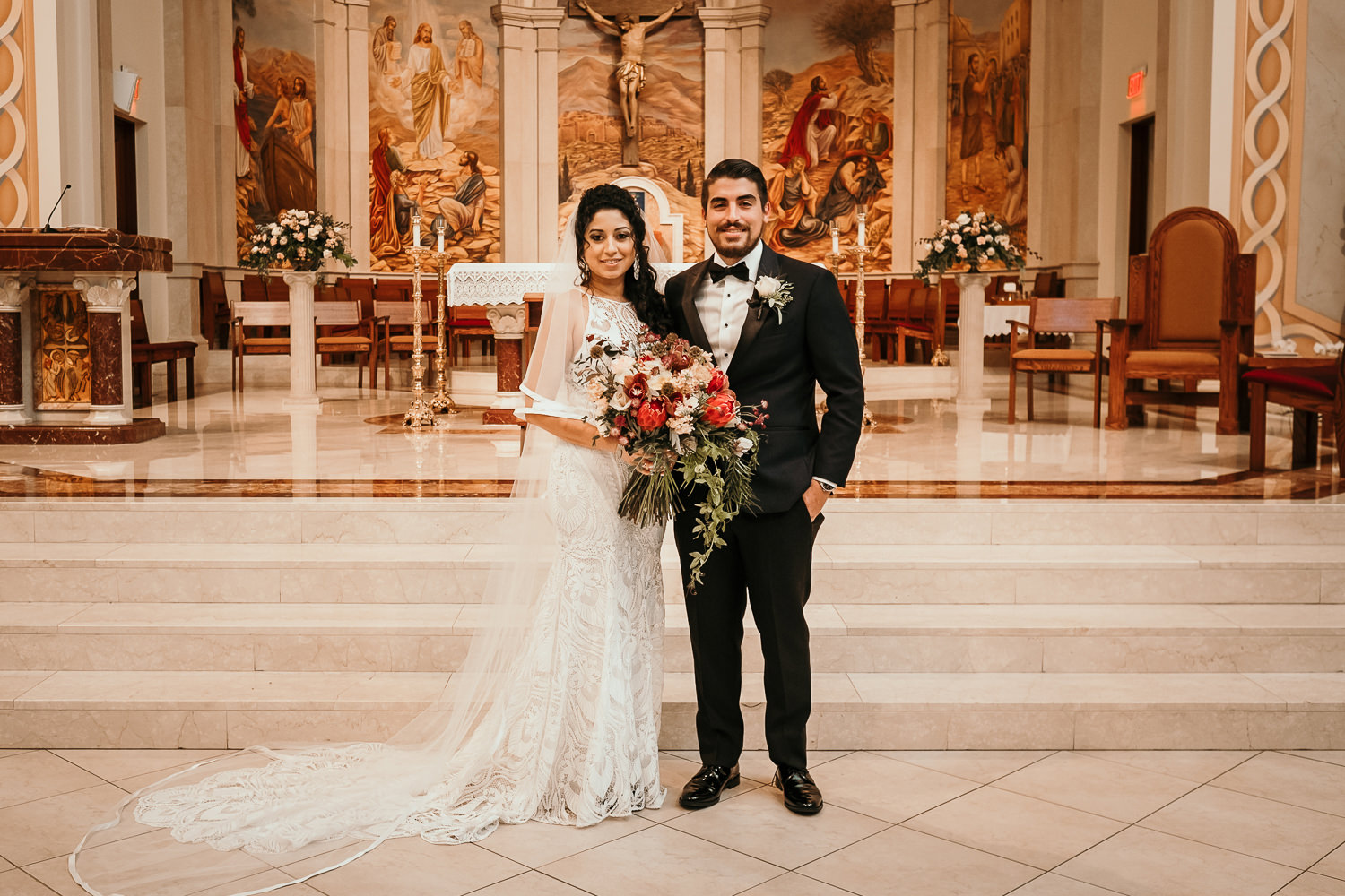 newlyweds posing in front of church altar