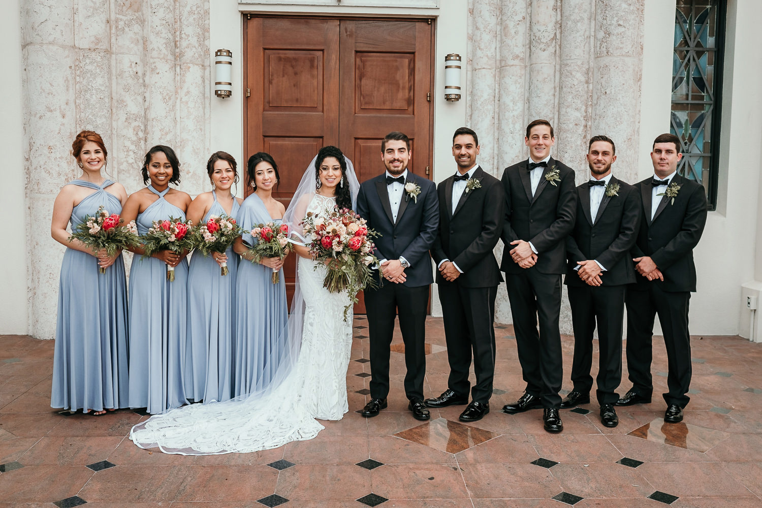 bridal party posing in front of wooden church doors