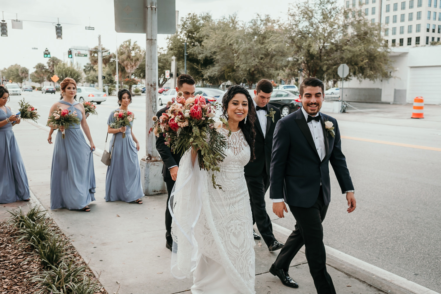 bridal party walking laughing on sidewalk