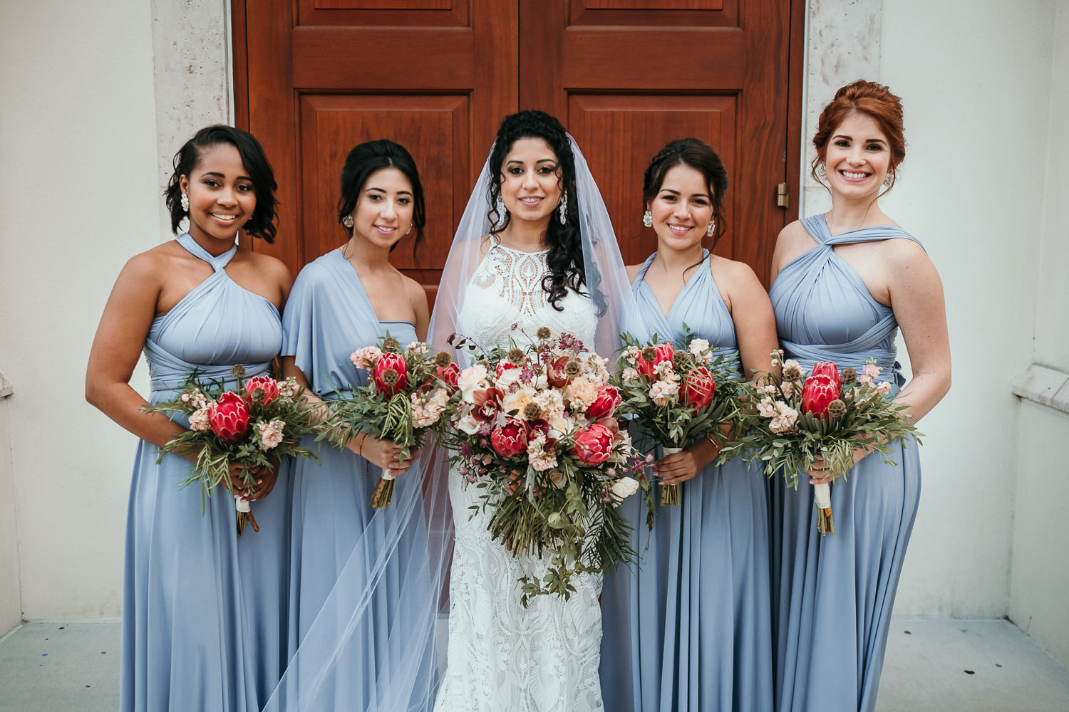 bride posing with bridesmaids wearing blue dresses holding flowers