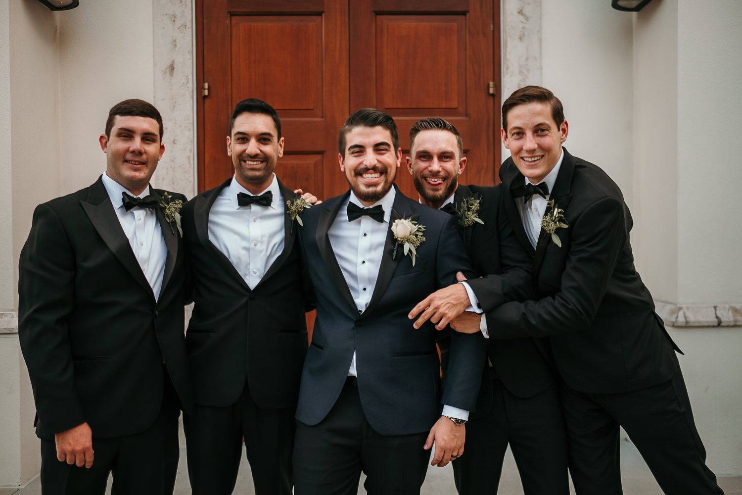 groomsmen hugging in front of wooden church doors