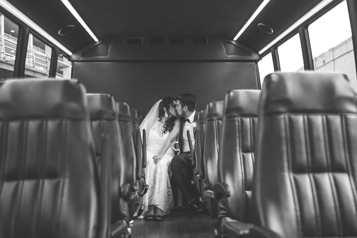 newlyweds in the back of a bus kissing