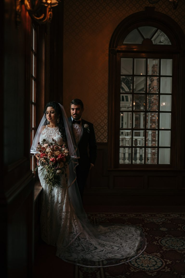 dark moody picture of bride looking out window with groom
