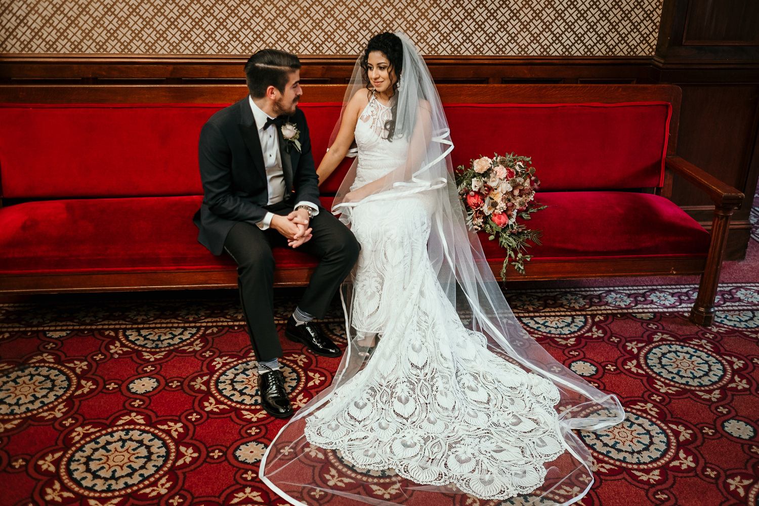 bride and groom holding hands sitting on red velvet couch