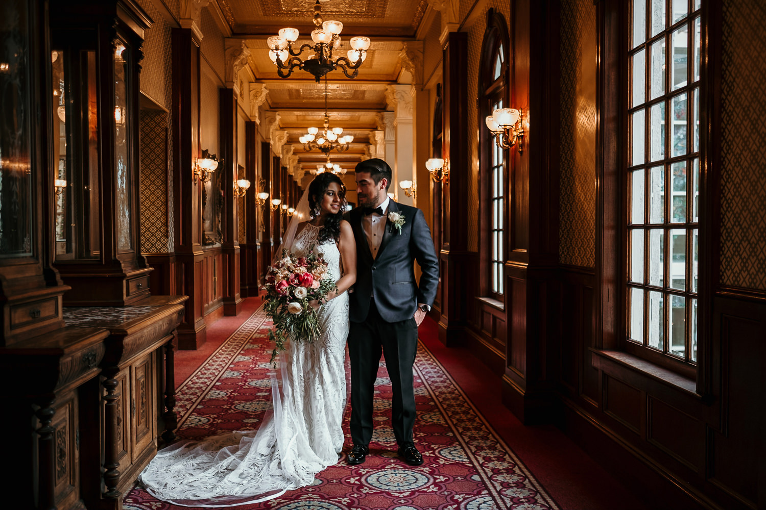 newlyweds posing in hallway of ballroom at church street