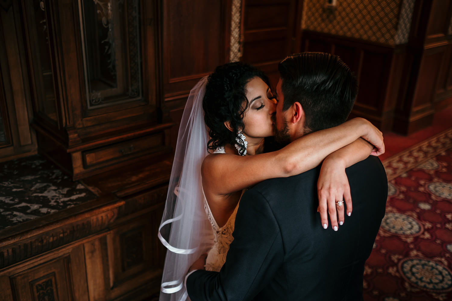 overhead shot of bride with arms over grooms shoulders kissing