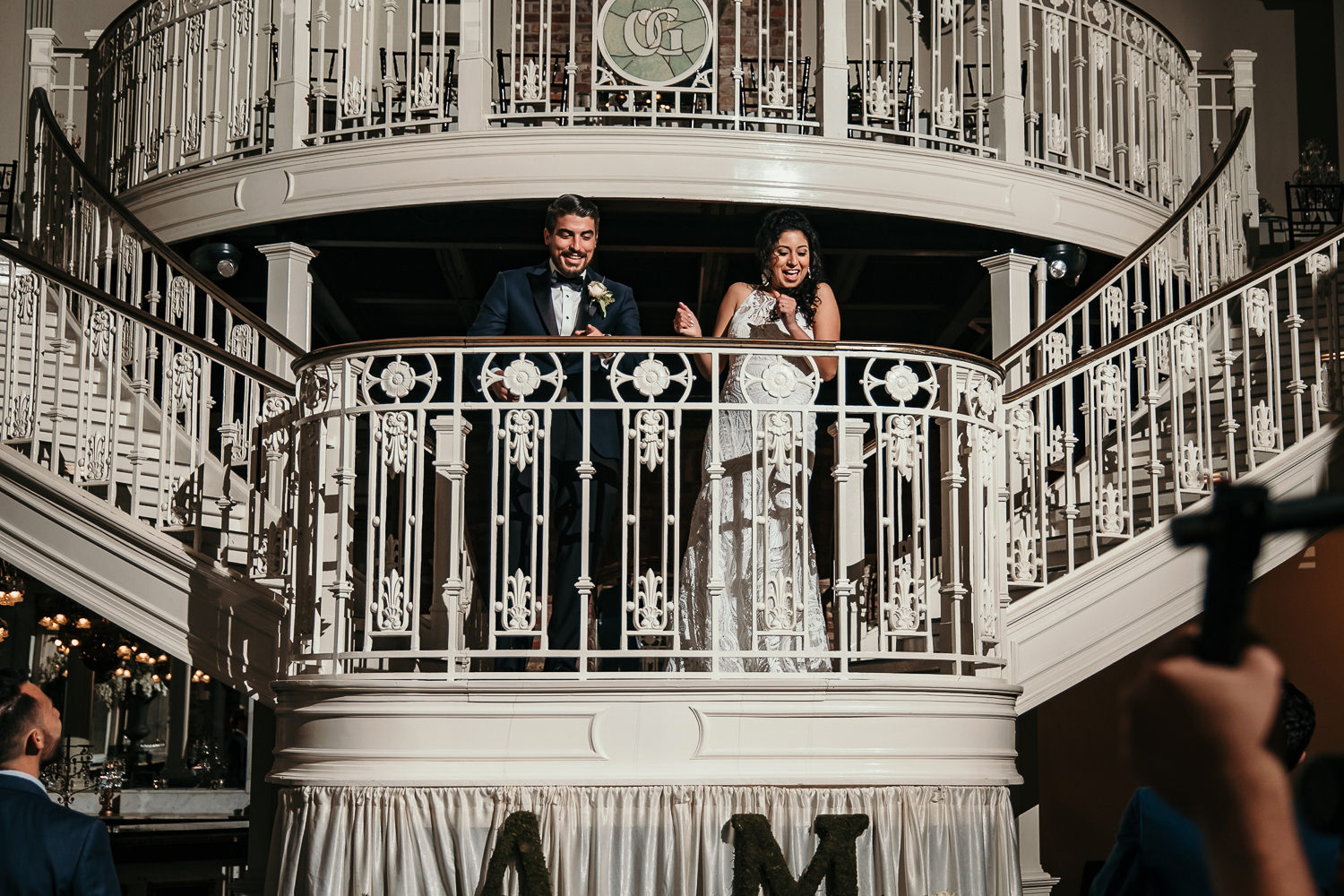newlyweds on balcony smiling at cheering crowd