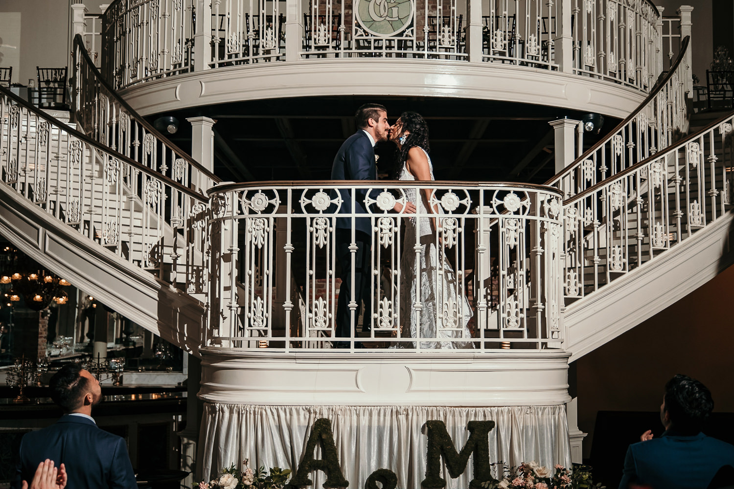newlyweds kissing on orchid garden balcony during reception