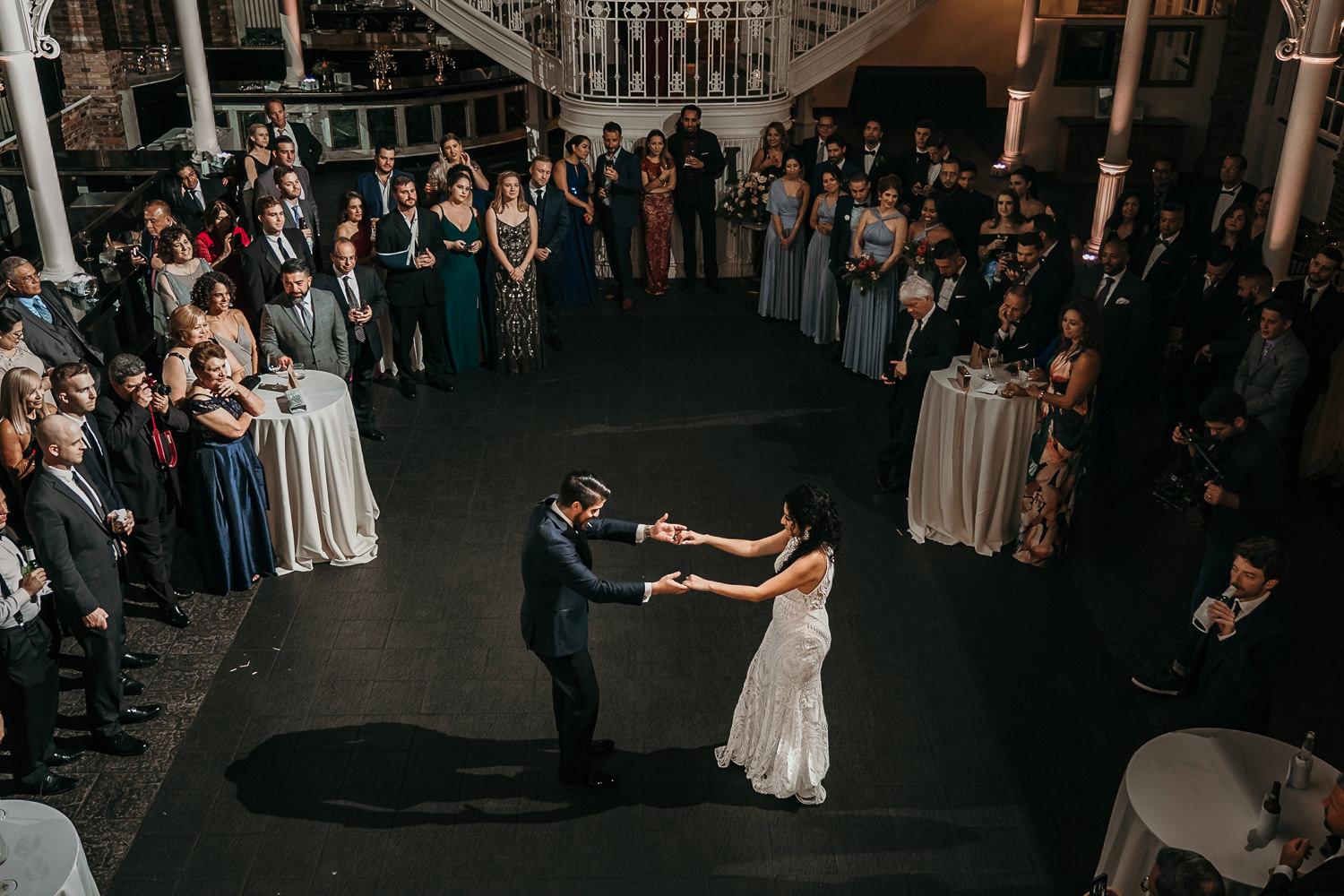 wide balcony shot of first dance bride and groom holding hands