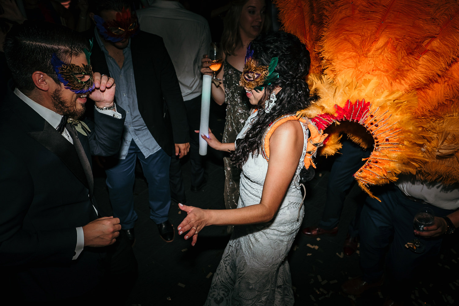 bride and groom wearing masquerade masks