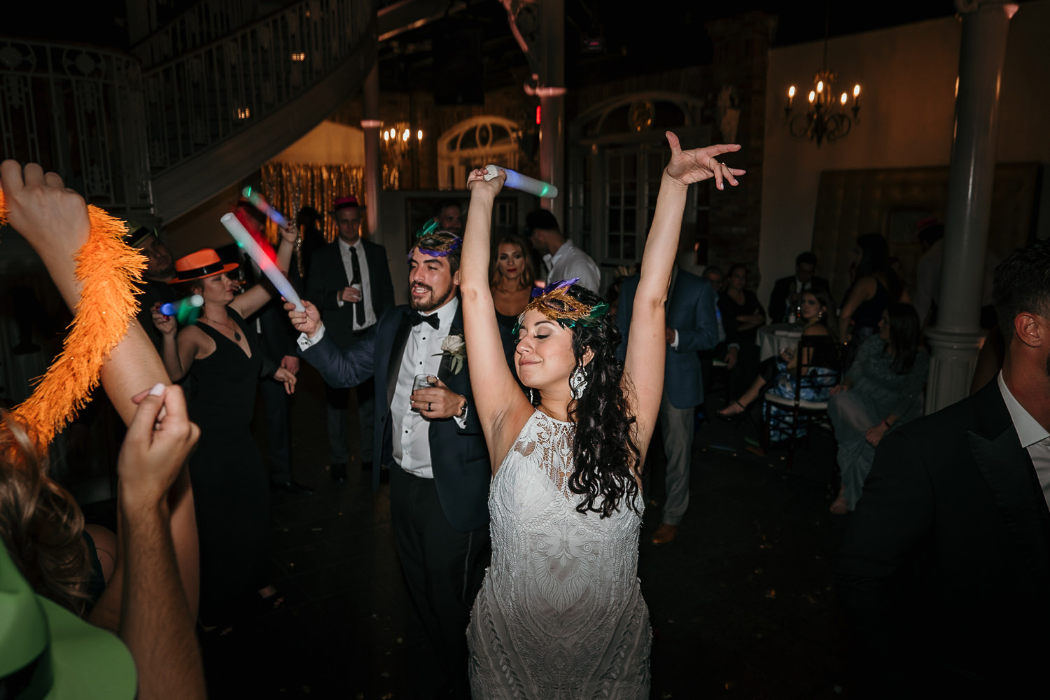 newlyweds together bride dancing hands in air masquerade mask on head