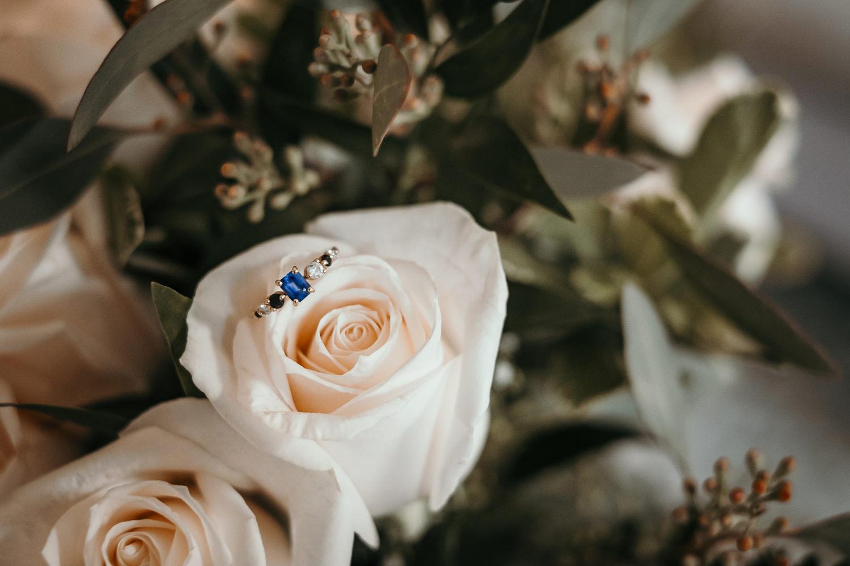 macro of wedding ring on white flower