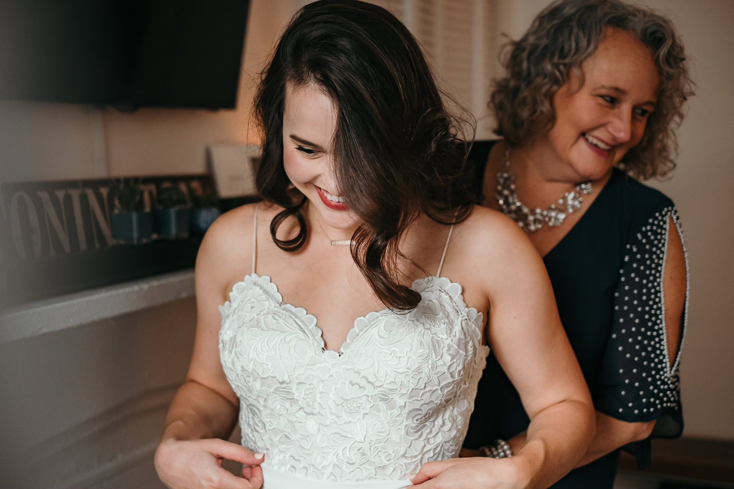 bride laughing grandmother behind her helping with dress