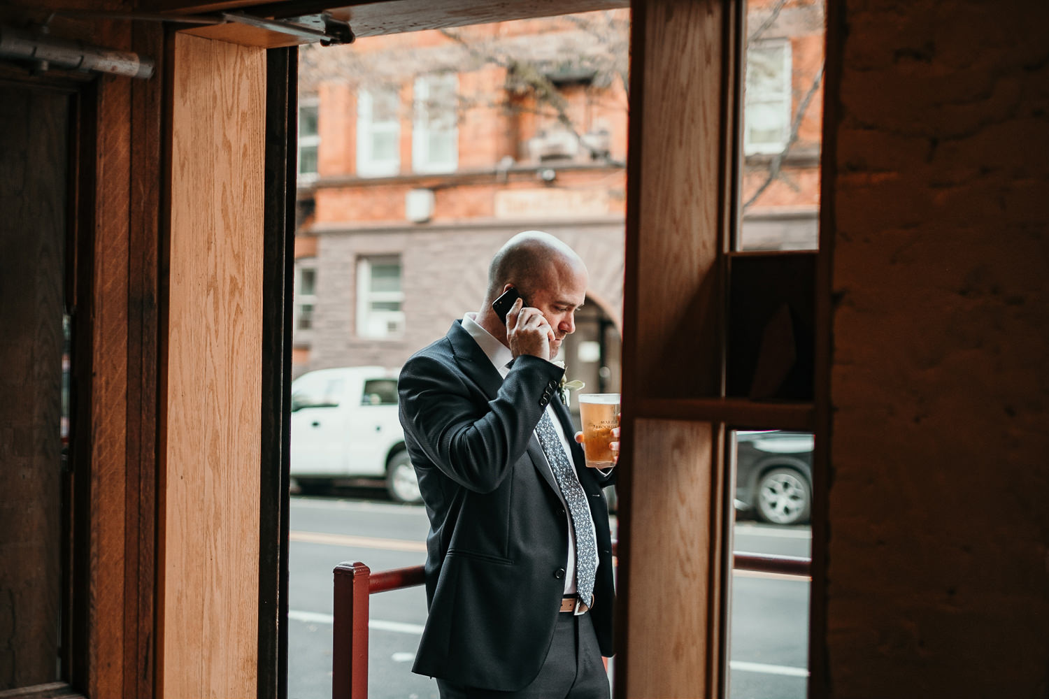 groom outside of bar on phone holding beer