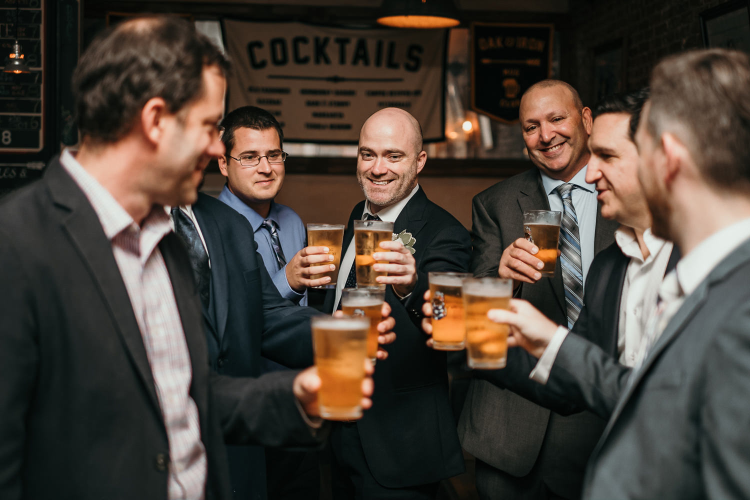 groom and groomsmen toasting with beer glasses