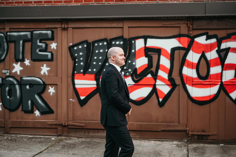groom walking by graffitied wall
