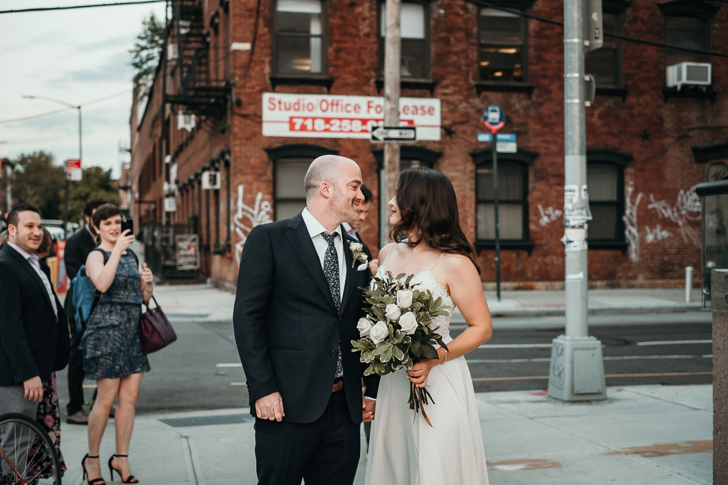 bride and groom stare at each other on brooklyn street corner