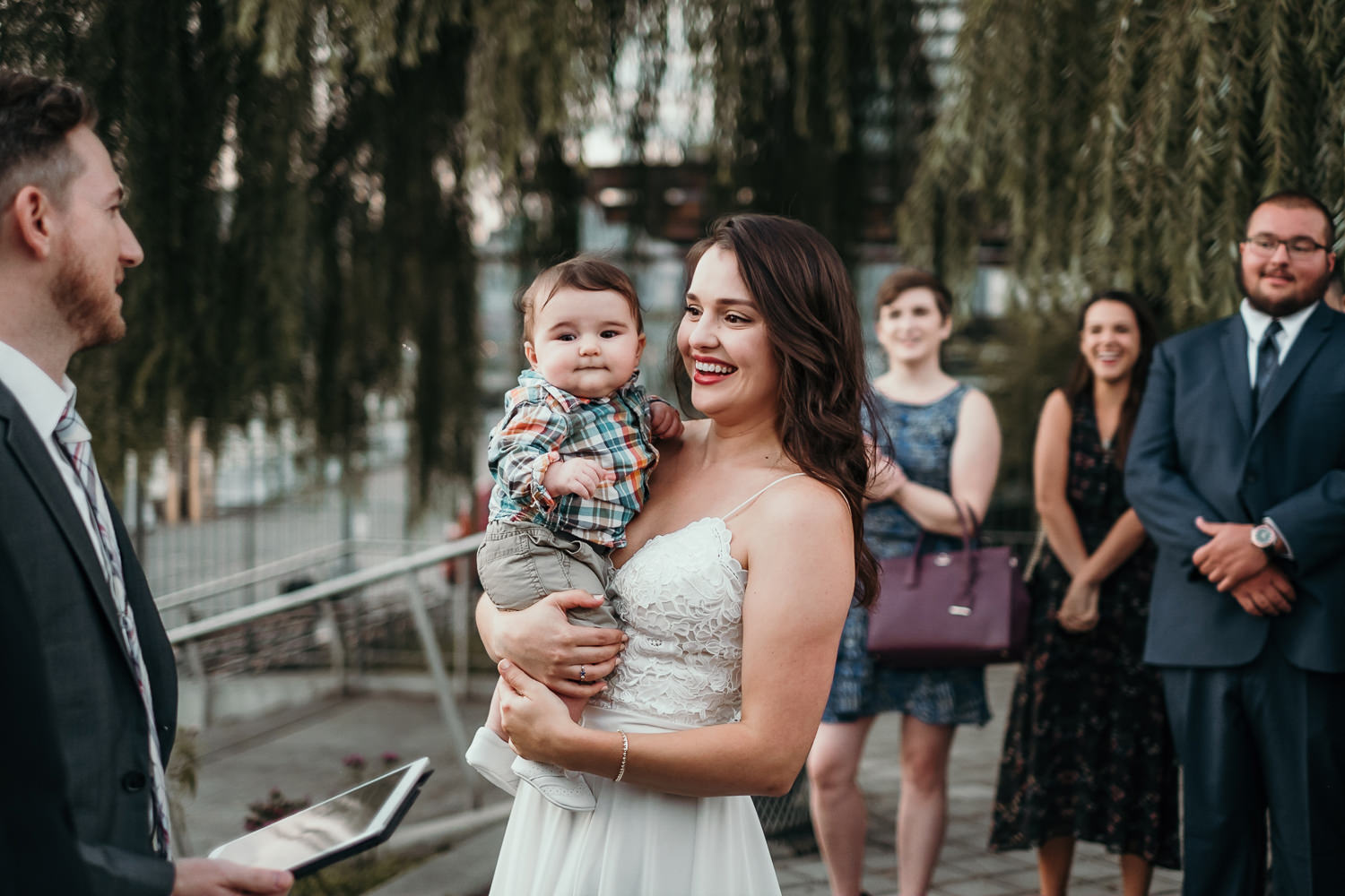 bride smiling holding baby at ceremony spot
