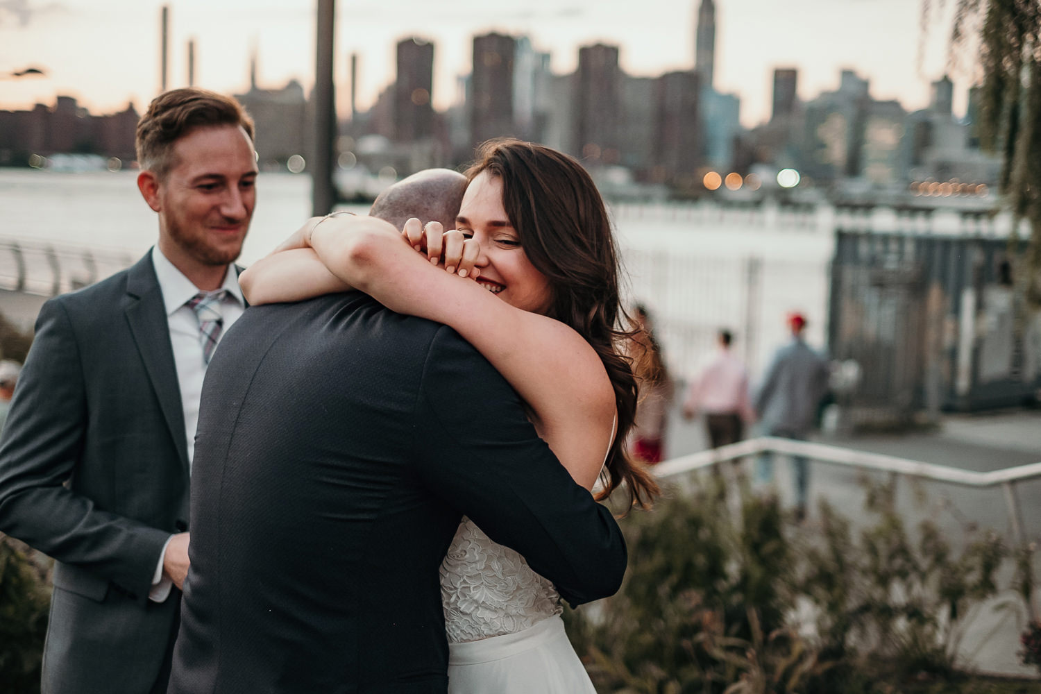 newlyweds tightly hugging bride smiling