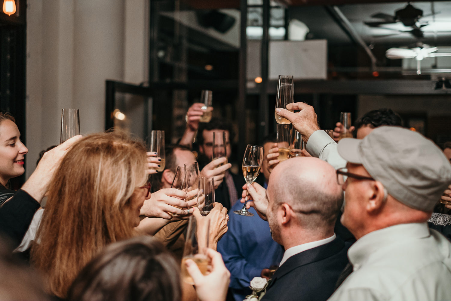 wedding guests at bar cheering with champagne
