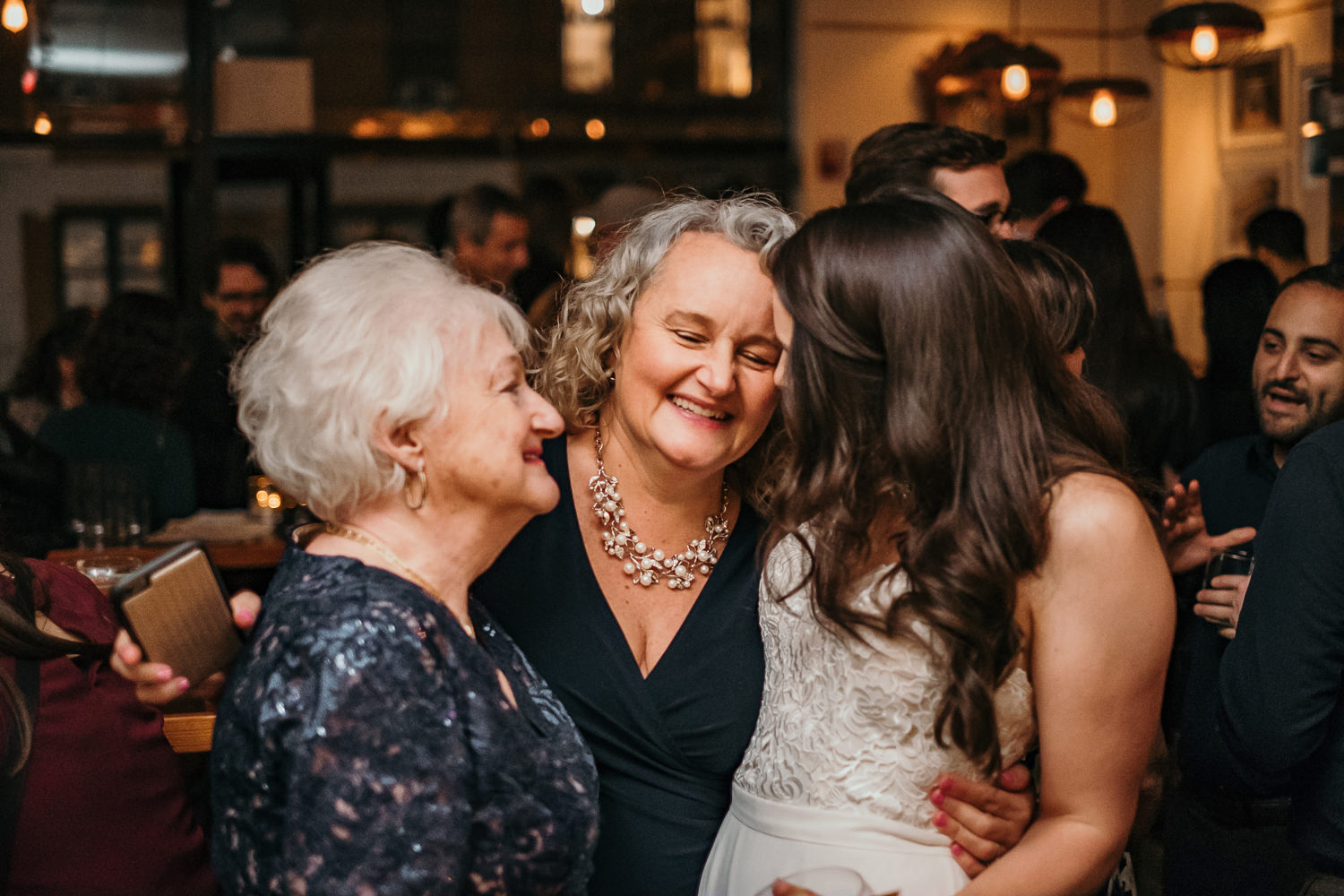 grandmother mother and bride hugging laughing
