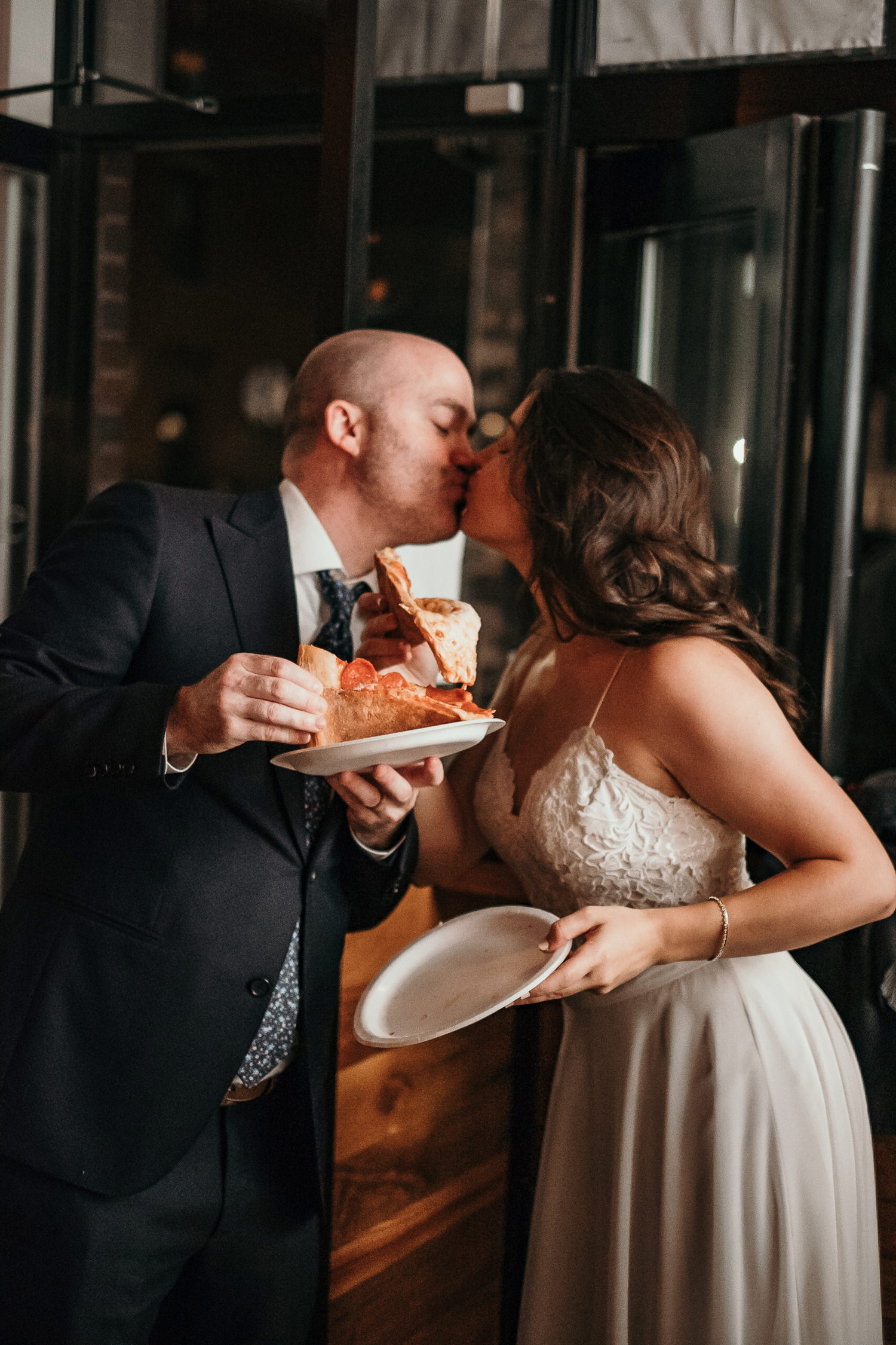 bride and groom kissing holding pizza