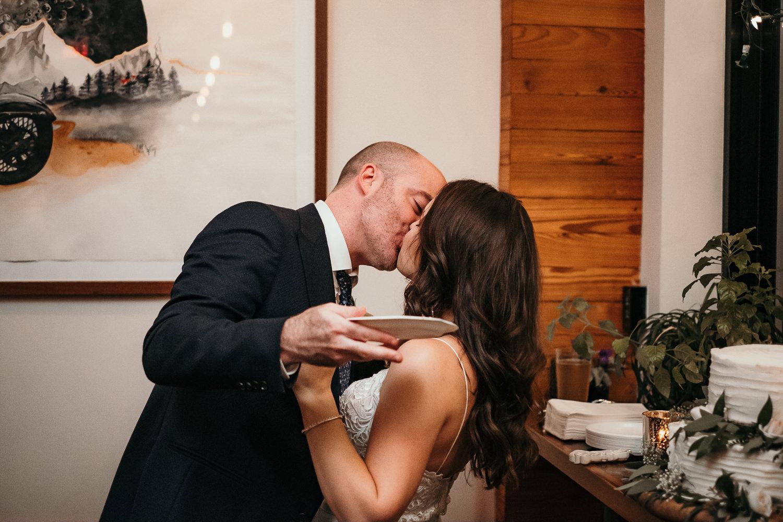 newlyweds kissing holding cake plate
