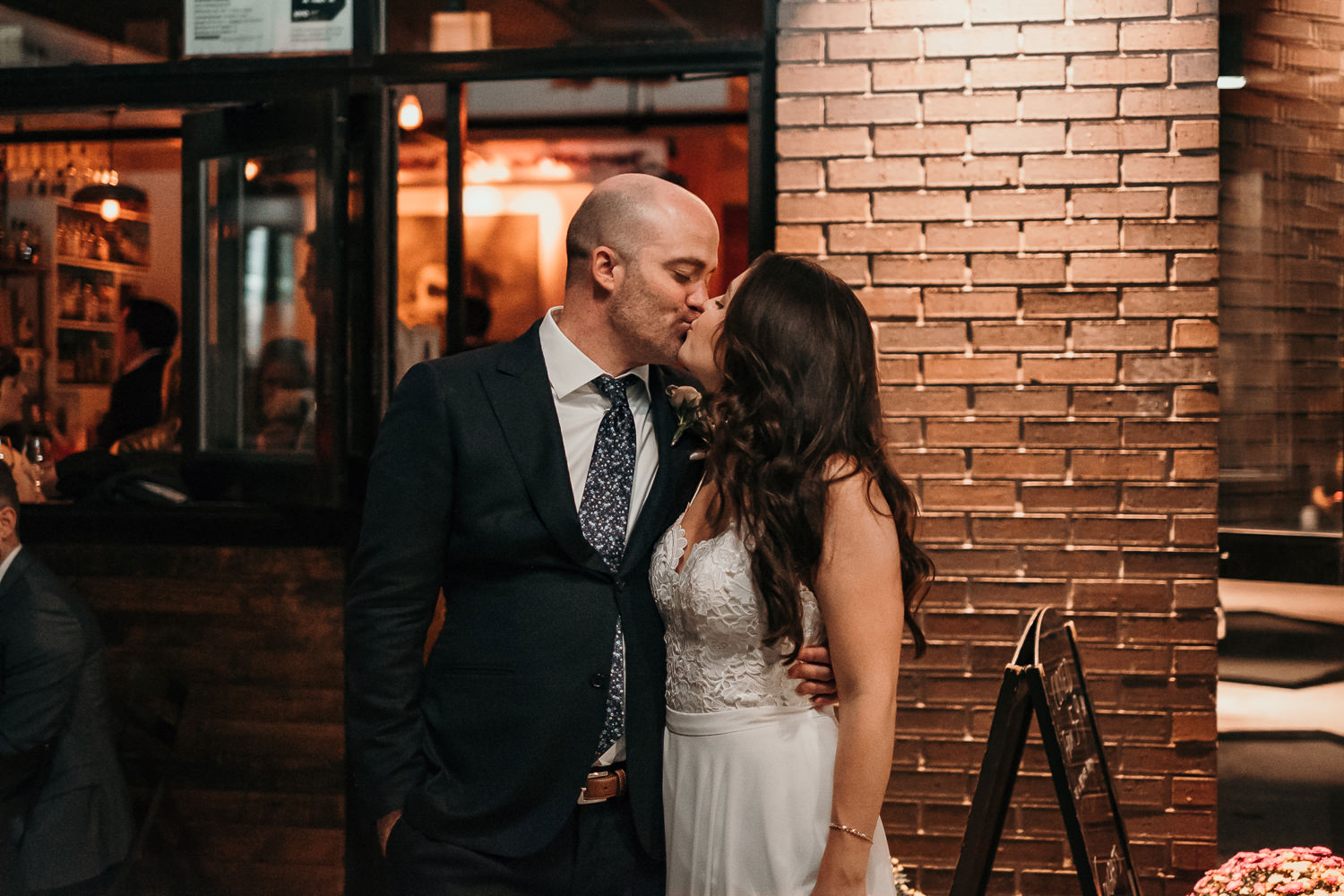 newlyweds kissing outside bar lit by street lights