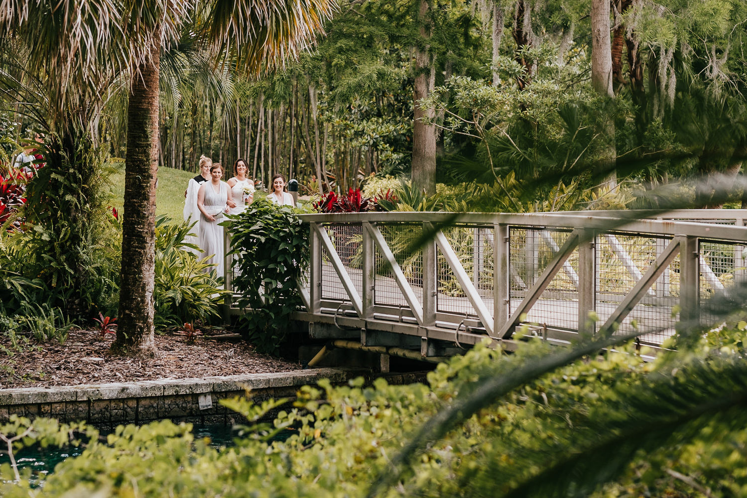wide shot of bride and bridesmaids walking on bridge