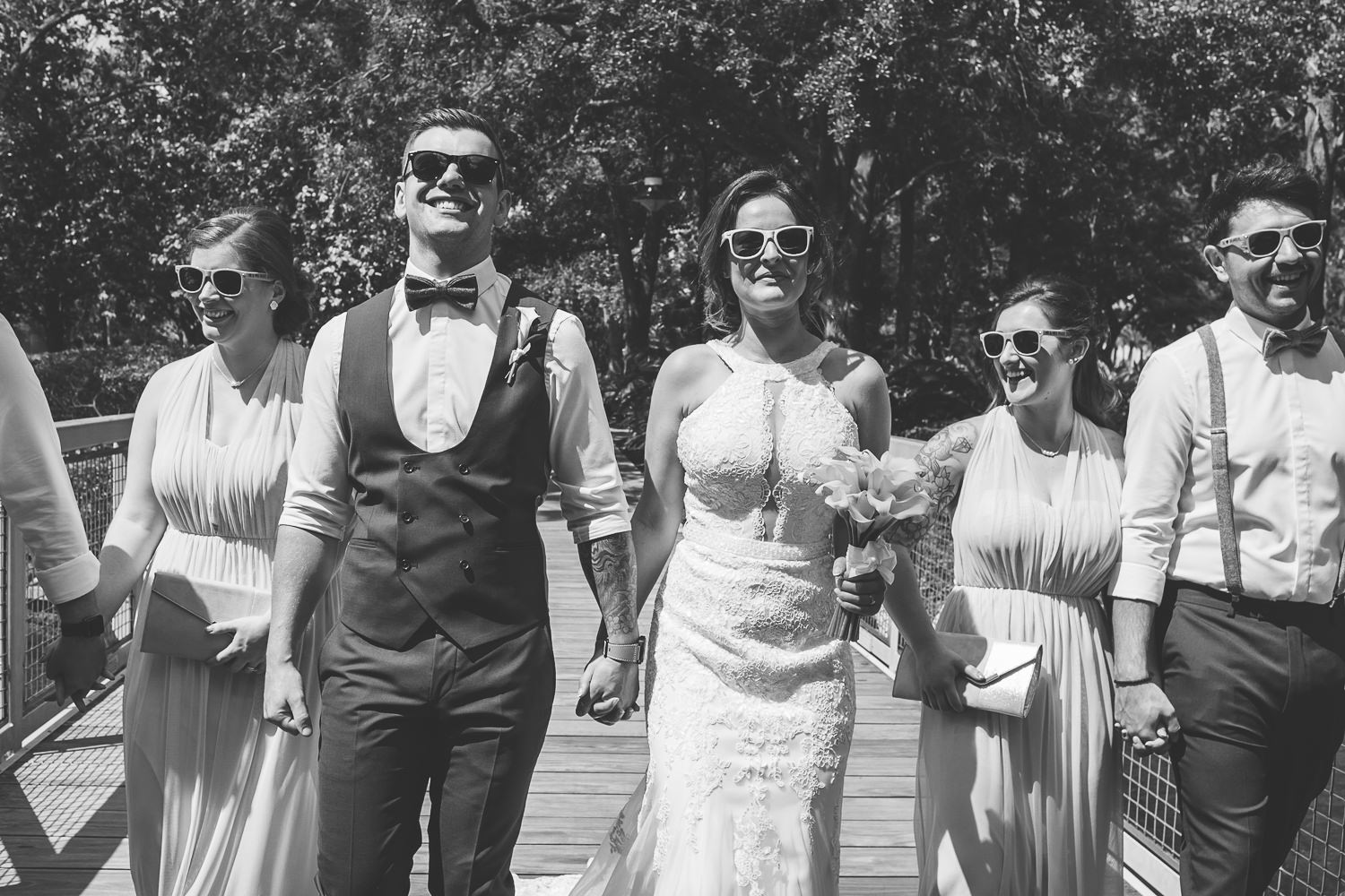 black and white bridal party on bridge wearing sunglasses