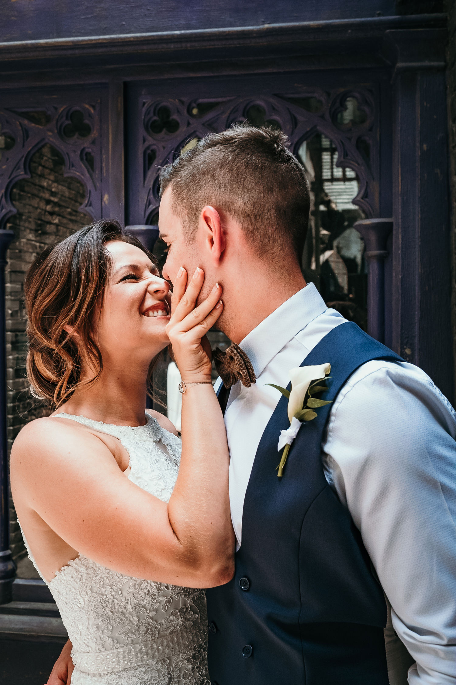 close up of bride squeezing grooms face