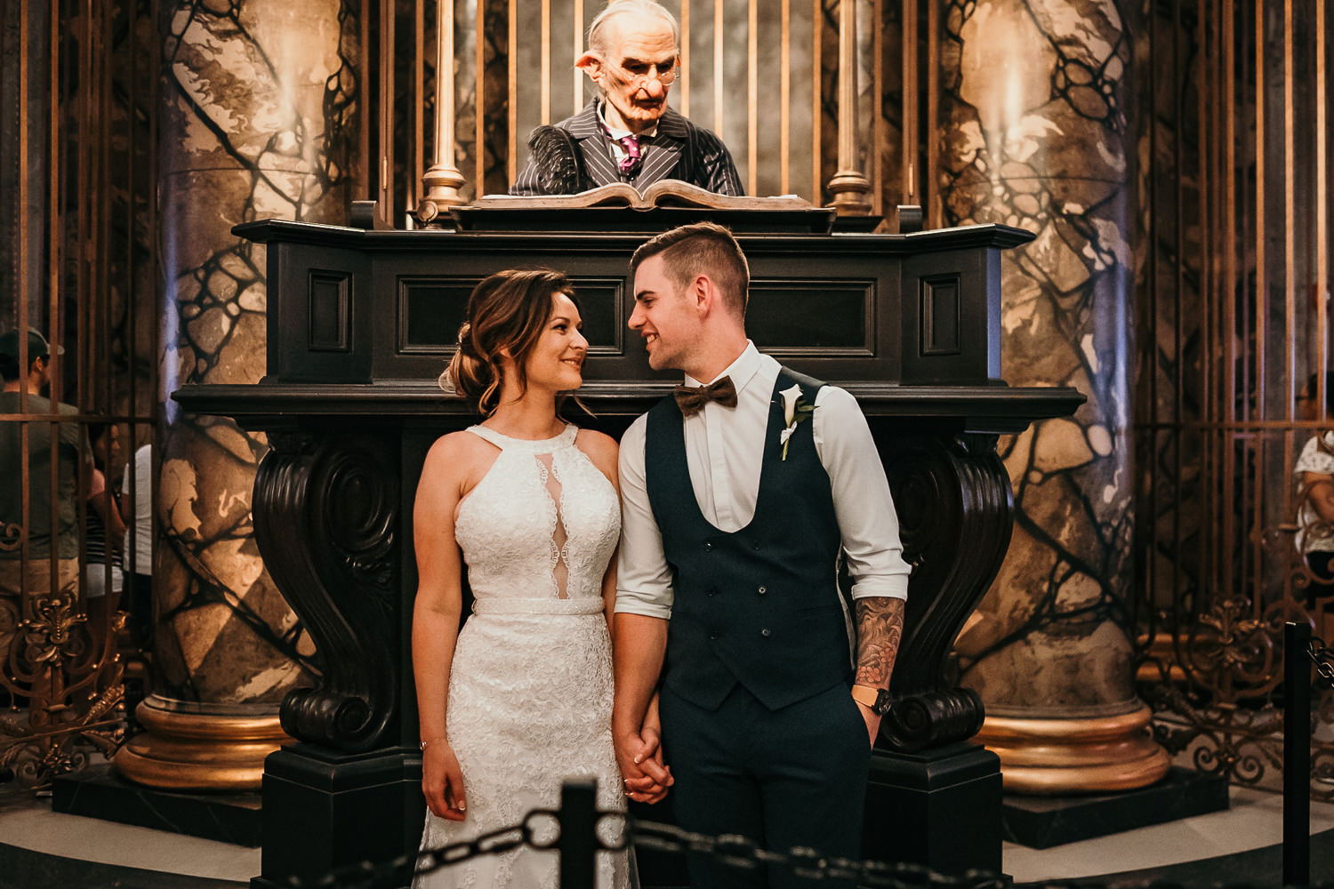 newly married couple posing in front of gringotts elf
