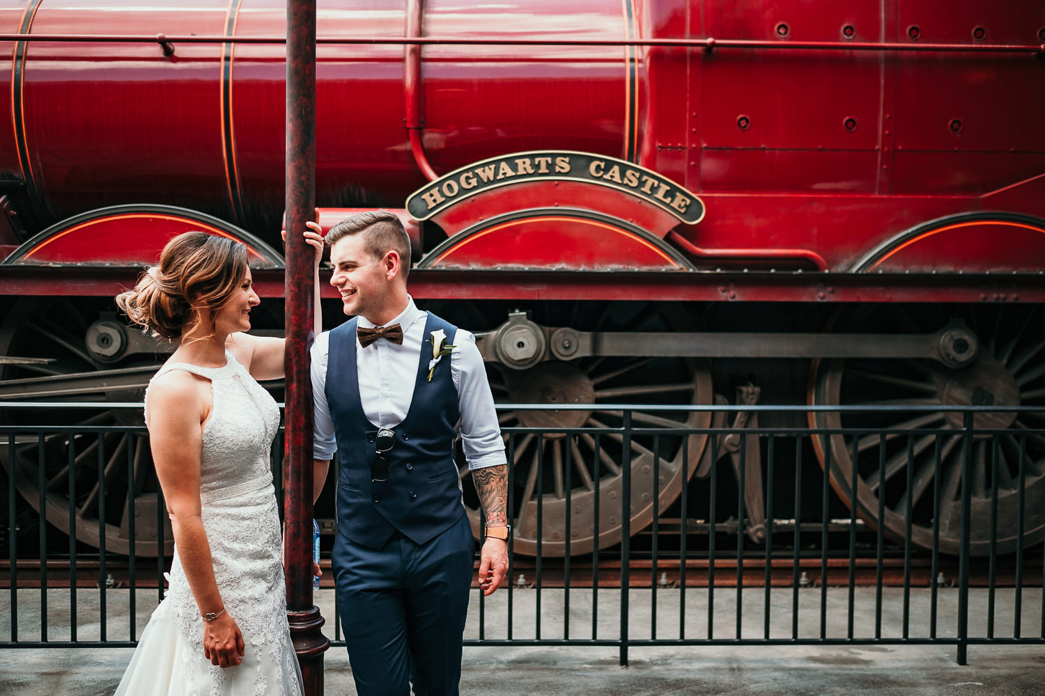 newlyweds posing in front of hogwarts express train