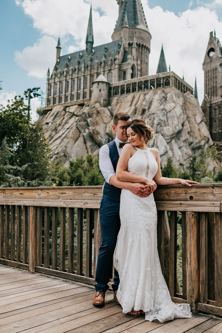 newlyweds hugging in front of hogwarts castle