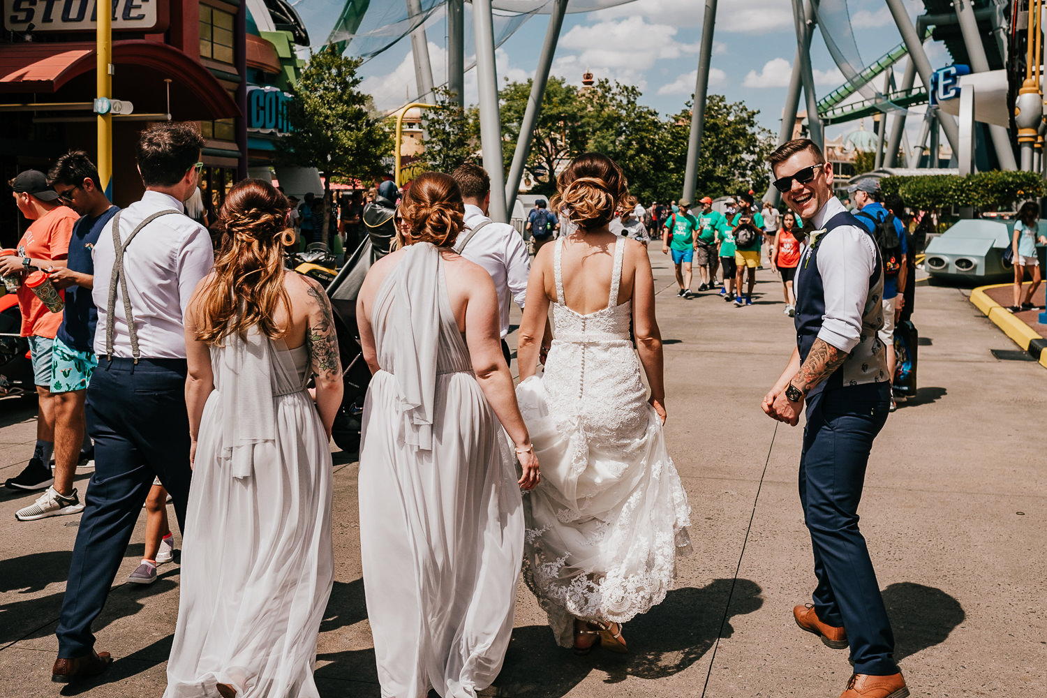 bridal party exiting island of adventure groom looking back smiling