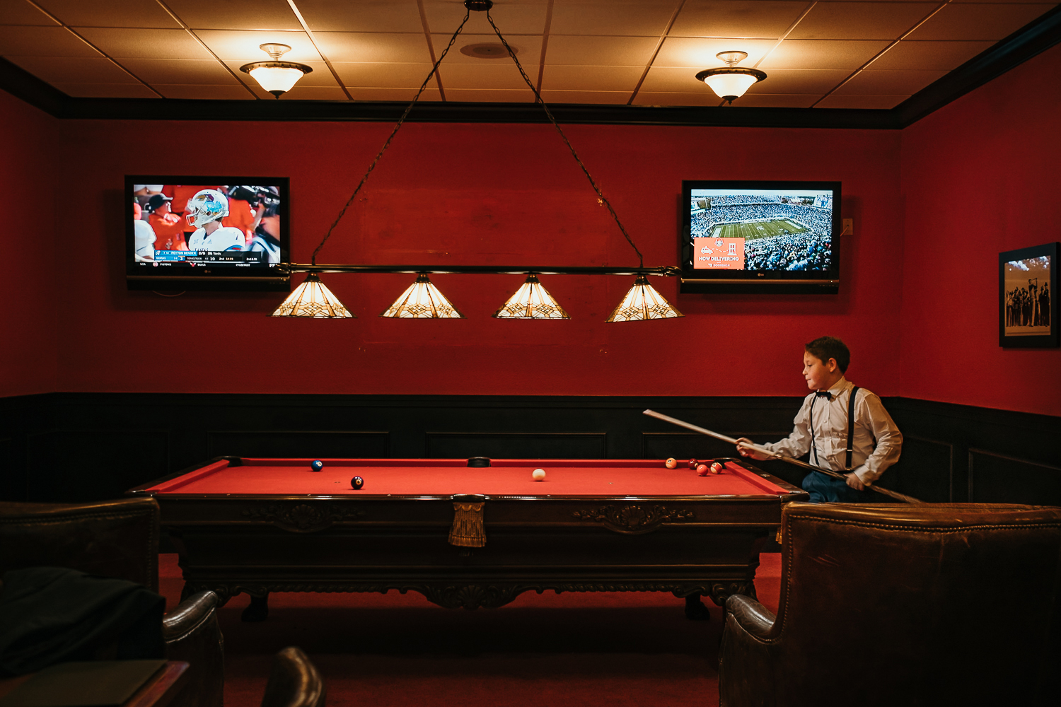 wide side shot of kid playing pool dressed formally with a red pool table