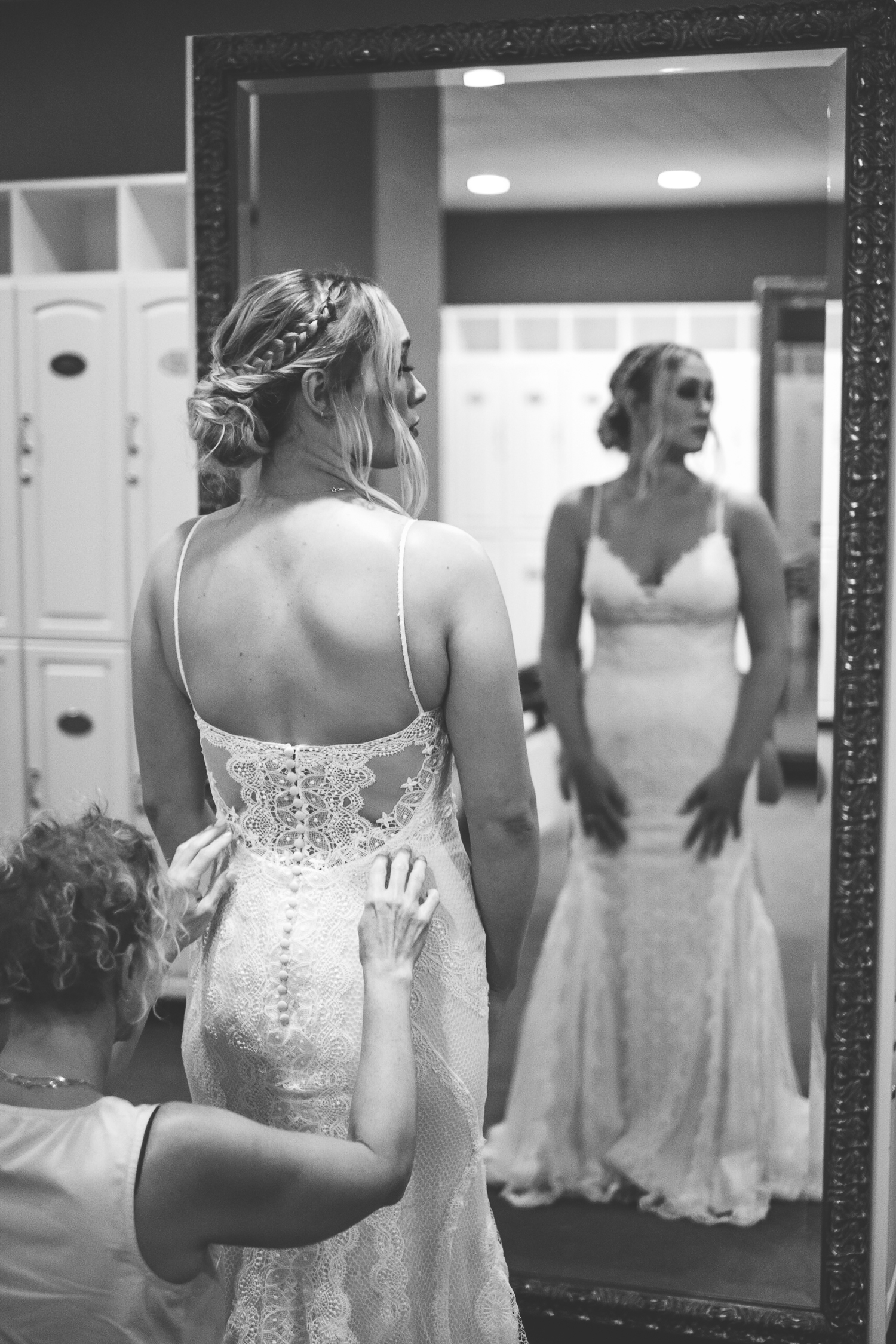 black and white mom fixing the brides wedding dress with mirror