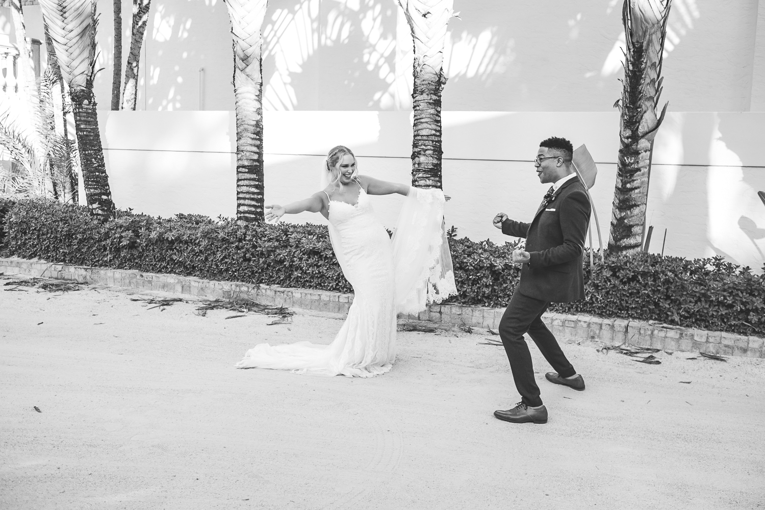 black and white wide shot of bride and groom dancing being silly