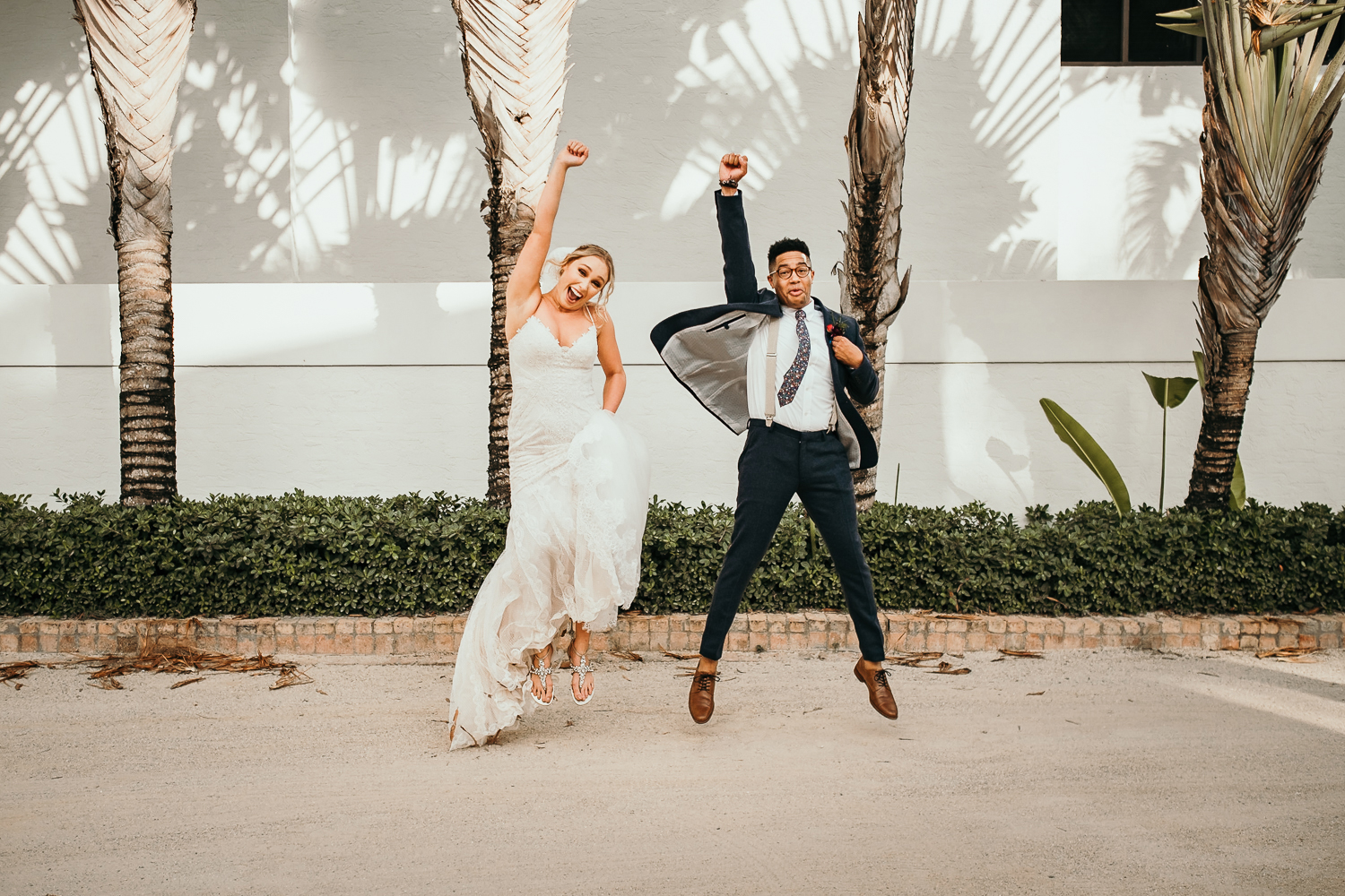 newlyweds jumping in air outside of wanderers club