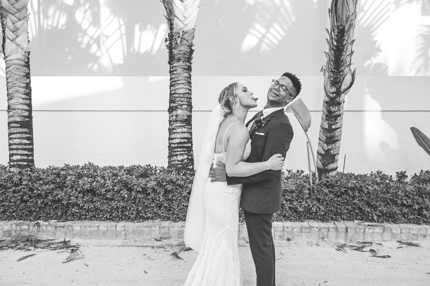 bride trying to lick grooms face with groom pulling away