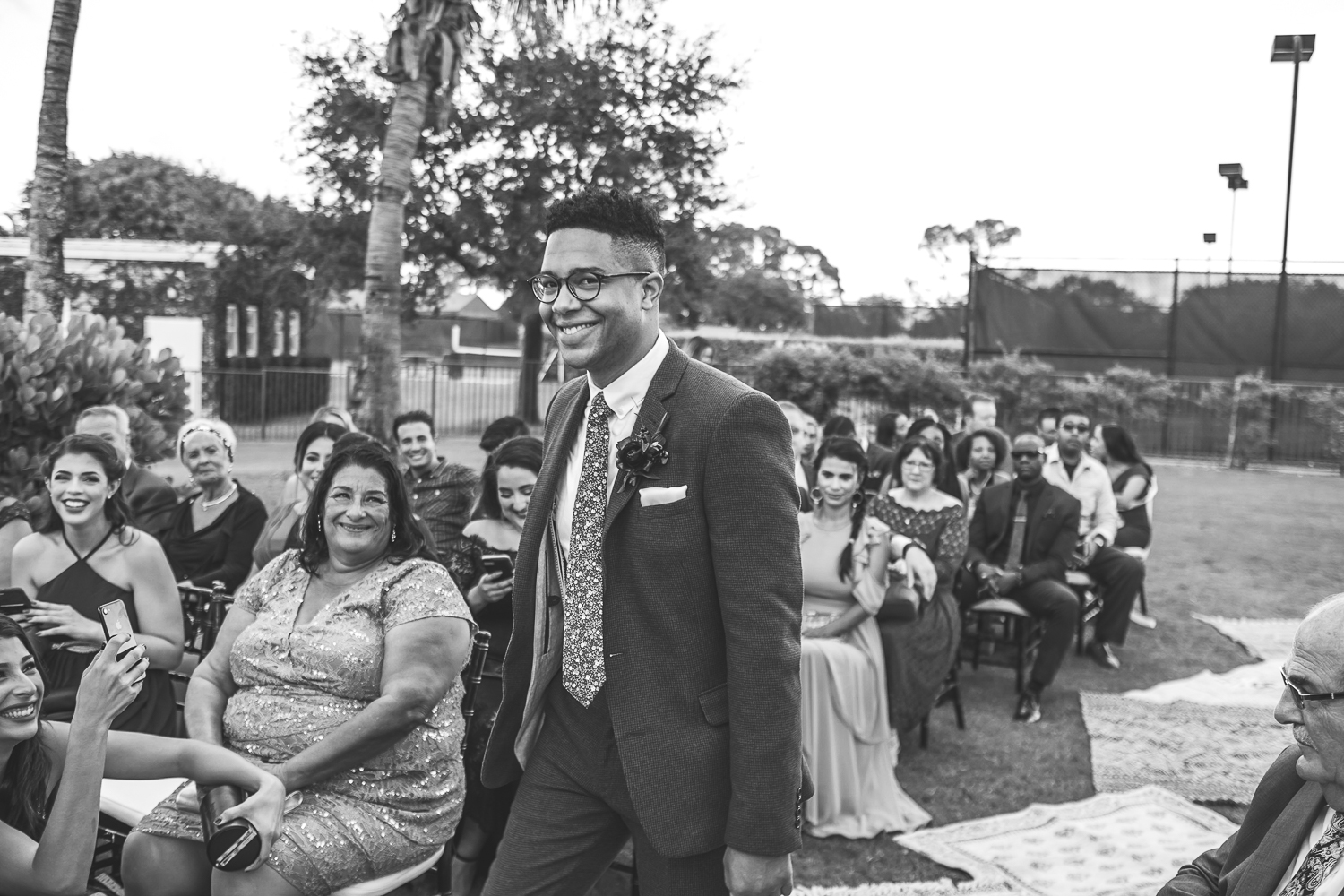 groom walking down aisle smiling at camera