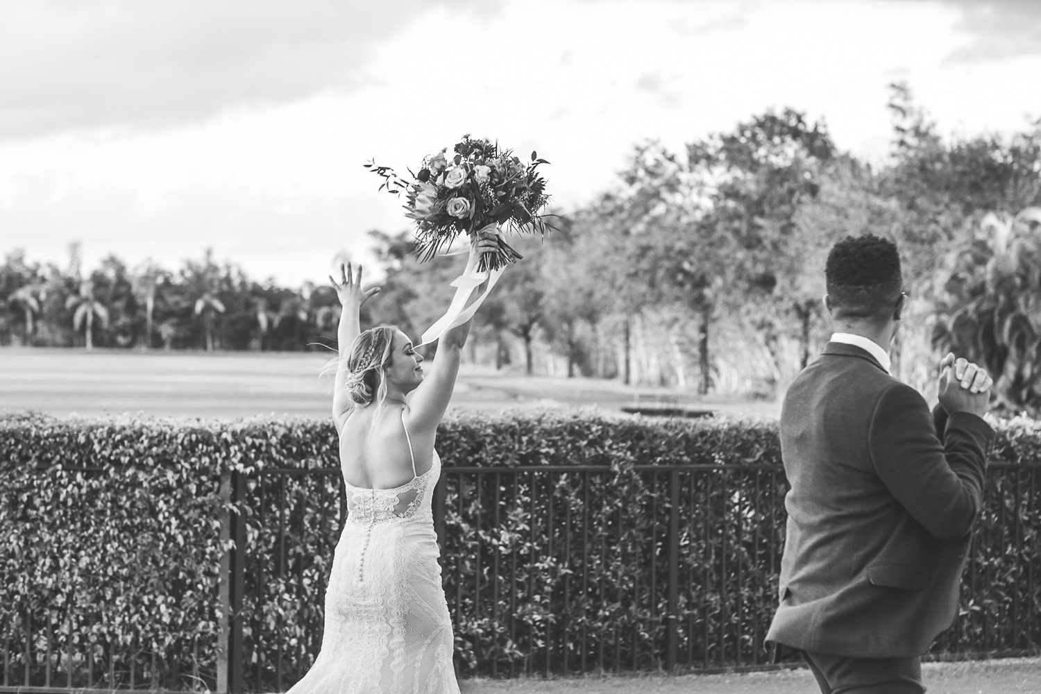 wide shot of bride with both her arms in the air holding bouquet