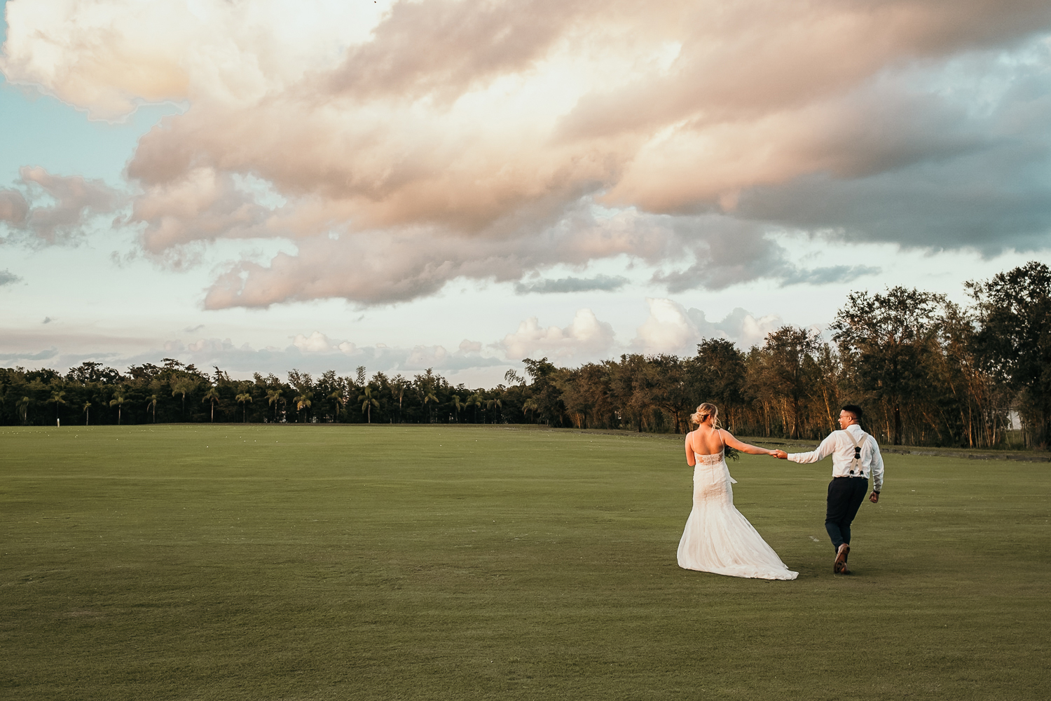 wide shot of bride and groom running into sunset empty golf course