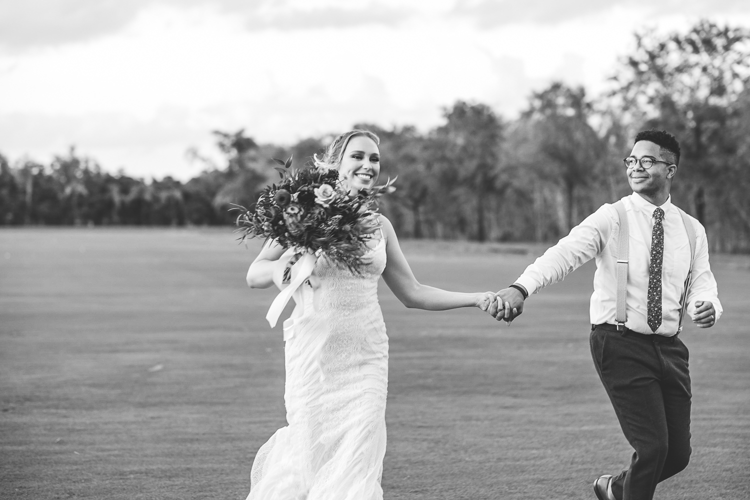newlyweds running into sunset black and white