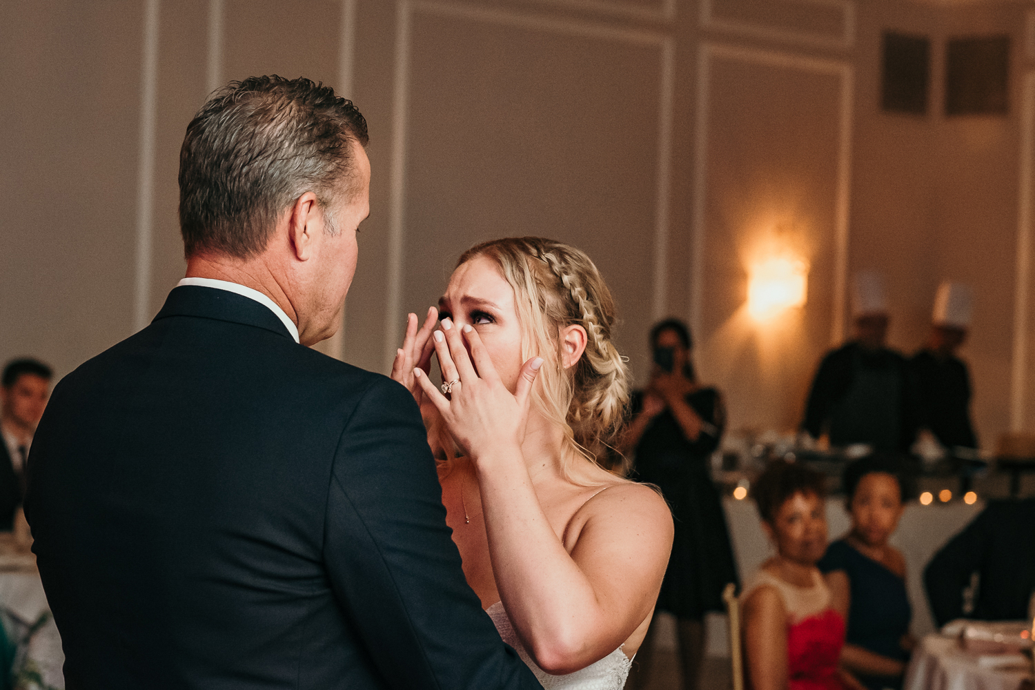 close up of bride wiping her tears from dads point of view